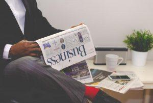 Ilustrasi orang menimbang risk reward investasi dengan membaca koran bisnis